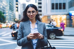 Young attractive ethnic business woman in gray jacket using mobile phone and smiling while crossing road in New York City on daytime