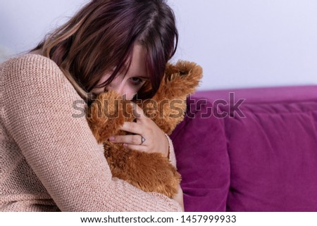 Young attractive european woman sitting home living room couch feeling sad tired and worried suffering depression in mental health problems and broken heart concept.