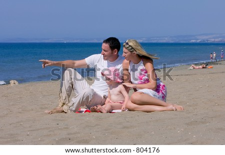 Young attractive family on beach vacation in Spain on a sunny day with man pointing out to sea