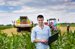 Young attractive farmer with laptop standing in corn field, tractor and combine harvester working in wheat field in background