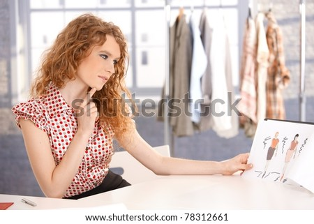 Young attractive fashion designer working in office at desk thinking.?