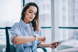 Young attractive female checking time of wrist watches while sitting in office interior holding mobile phone in hands. Brunette woman employee waiting for coffee break during long work day