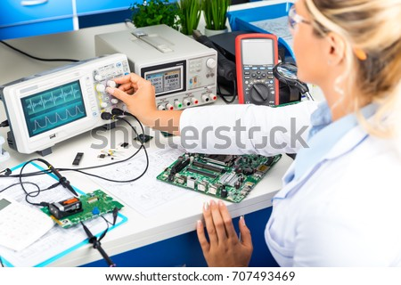 Young attractive female electronic engineer using digital oscilloscope in the laboratory #707493469