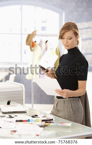 Young attractive female fashion designer working at office desk, using mobile phone, looking at paper.