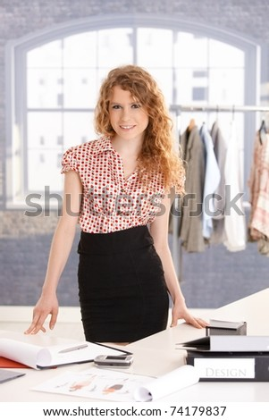 Young attractive female fashion designer working in office at desk, smiling.?