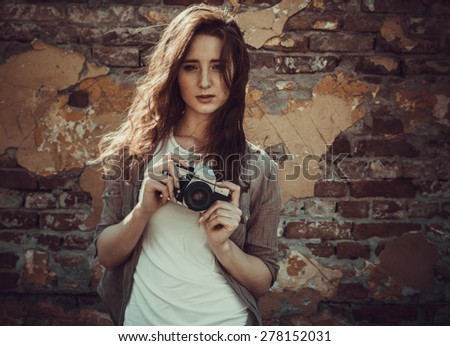 Young attractive female fashion model standing by the brick wall and holding retro camera.