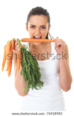 young attractive female holds bunch of carrots and try to eat one of them, isolated on white