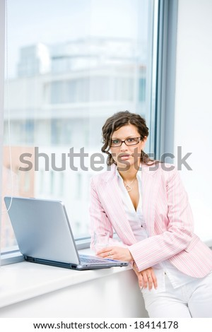 Young attractive female office worker working on laptop computer in fron front of office window.