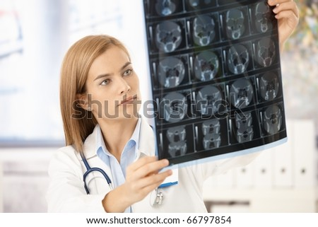 Young attractive female radiologist looking at x-ray image.?