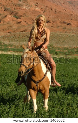 young attractive female rides horseback in red canyon region of southern utah