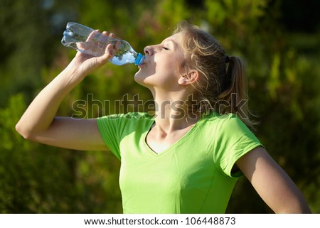 Young attractive female runner holds blue bottle of water