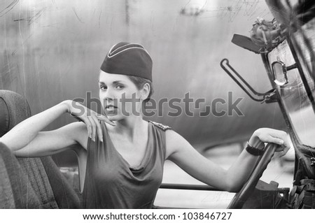 Young attractive female soldier driving the car (WARNING! There are noise, dust and scratches on the image)