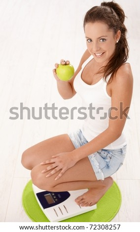 Young attractive female squatting on scale, holding an apple in hand, smiling, dieting.?