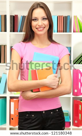 Young attractive female student holding her school books in library