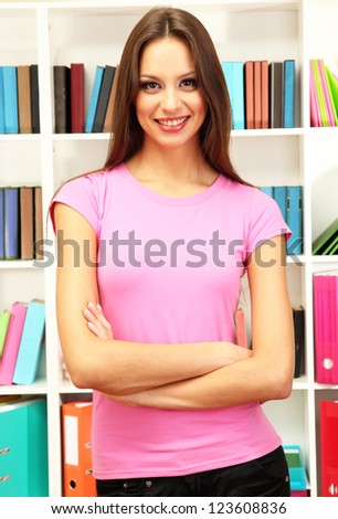Young attractive female student in library