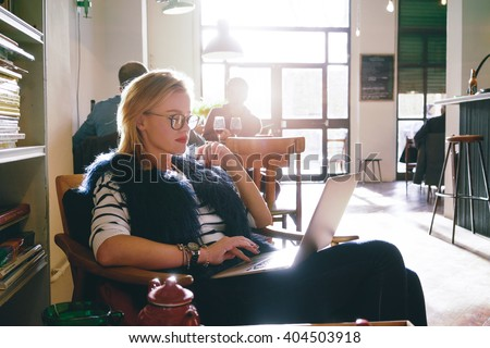 young attractive female student preparing for the exam using laptop while as drinking tea in a cafe. beautiful business woman using a laptop for the distance learning