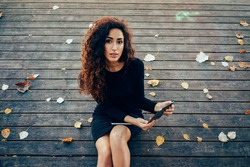 Young attractive female student with long curly hair using a smart digital tablet while relaxing in the park on a background of a wooden flooring