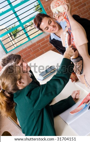 Young attractive female teacher teaching human anatomy at biology class