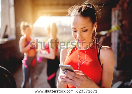 Young attractive fitness model listening music on smart phone charching positive energy before workout outside. Sun is shining and friends are behind preparing for training.
