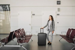 Young attractive girl at the airport in grey casual clothes, waiting with her backpack and baggage, smiling.