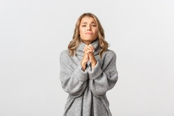 Young attractive girl begging for help, clenching hands together and pleased, saying please, standing over white background