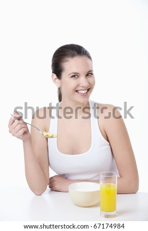 Young attractive girl breakfast corn flakes on a white background