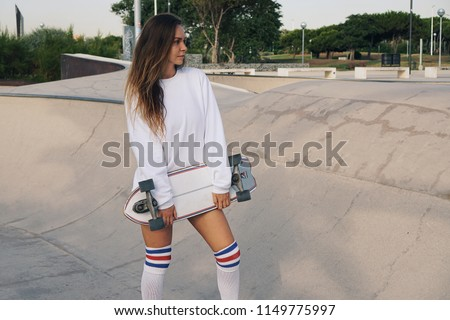 Young attractive girl in a white sweatshirt and knee socks in a skatepark with skateboard. 80s-90s spirit, Miami style. Mock up.