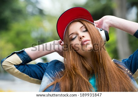 young attractive girl in urban background listening to music with headphones