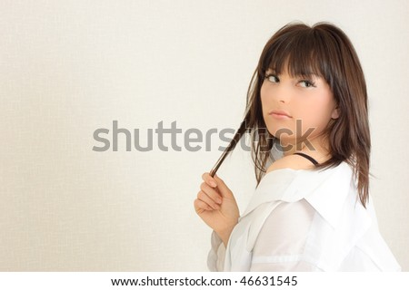 Young attractive girl plays with her hair against the white wall