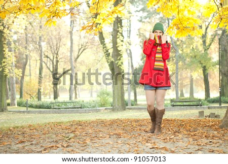 young attractive girl posing in cold autumn park
