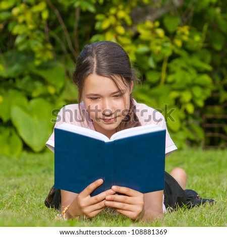 Young attractive girl reading book