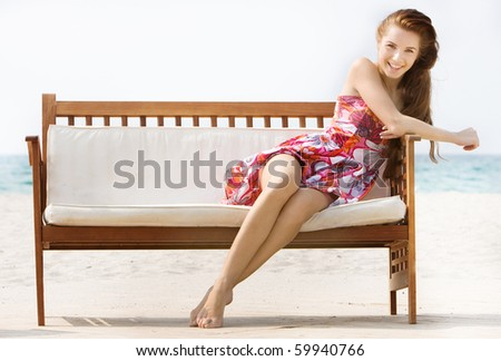 young attractive girl sitting on beach sofa over white