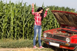 Young attractive girl standing beside broken car at rural road