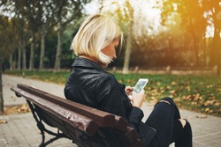 Young attractive girl using smartphone while sitting on a bench in the park, flare effects