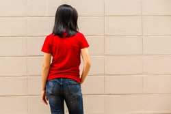 young attractive girl wearing a red t shirt standing on brick wall background