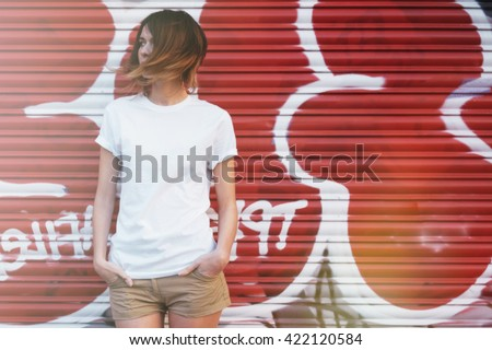 young attractive girl wearing a white t-shirt posing on a graffiti wall background