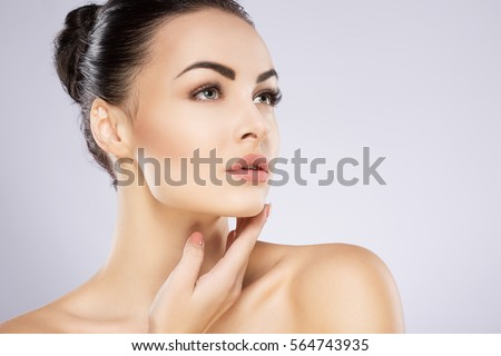 Stock Photo Young attractive girl with black hair fixed behind, big eyes, thick eyebrows and naked shoulders holding hand near face at gray background, portrait, copy space.