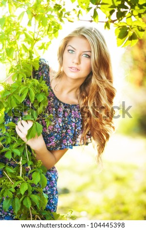 Young attractive girl with blue dress and blond hair outdoor on the field.Golden lady