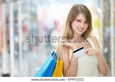 Young attractive girl with shopping and credit card in store