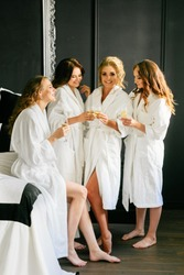 Young attractive girls talking and drinking champagne in white coats against a black wall
