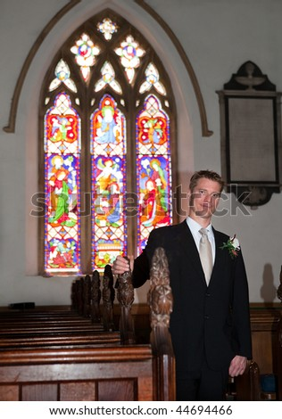 Young attractive groom waiting for his bride in church