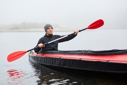 Young attractive guy having fun on kayak. Kayaking on river, attractive guy in boat sailing in river, holding oar in hands, looks into distance, spends cold foggy day canoeing.