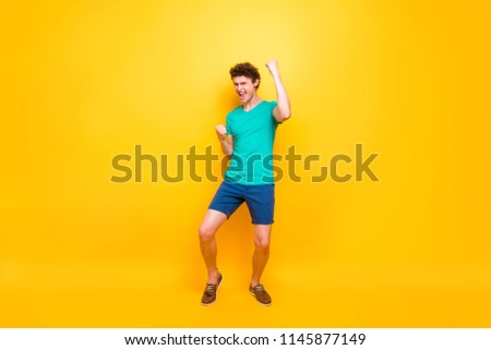 Young attractive handsome cheerful guy wearing casual green polo t-shirt and blue shirts, raising hands up celebrating winning. Isolated over vivid shine bright yellow background