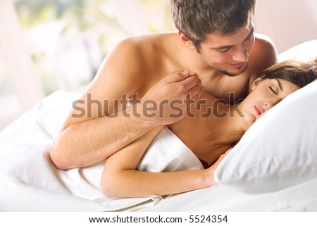 Young attractive happy amorous couple in bedroom
