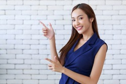 Young attractive happy Asian woman gesturing pointing at copy space, standing position at the office.
