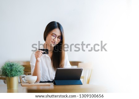 Young attractive happy Asian woman is using tablet for shopping and paying online by credit cards in her hand, online purchases content, commerce on the Internet shop background with white copy space.