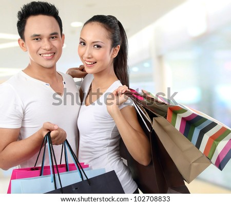young attractive happy couple at shopping mall
