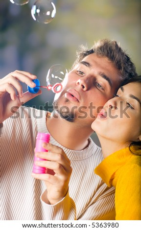 Young attractive happy couple blowing bubbles outdoors