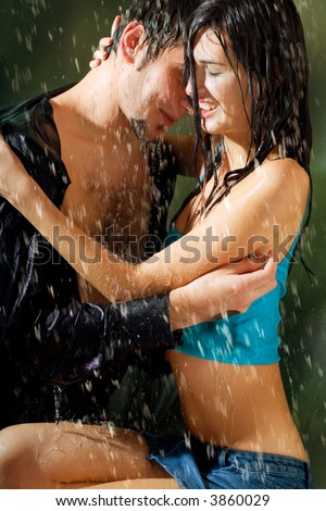 Young attractive happy smiling couple hugging under a rain, in passion