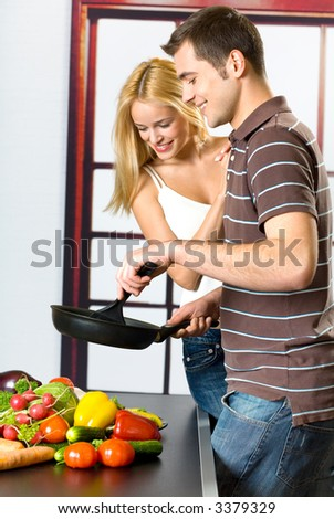 Young attractive happy smiling couple playfully cooking at kitchen